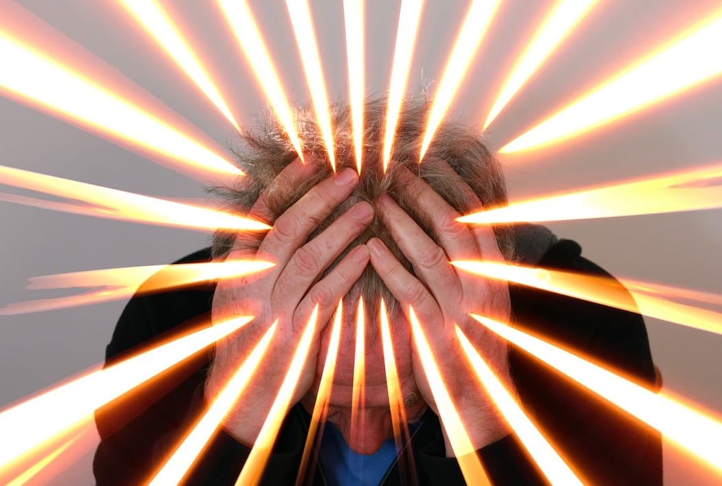 Man holding head in hands with beams of light appearing to radiate from head and hands